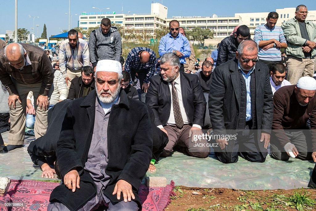 Israeli Arabs and Sheikh Raed Salah (front), the leader of the radical northern wing of the Islamic Movement in Israel, take part in a prayer in support for the release of Mohammed al-Qiq, a Palestinian prisoner on hunger strike, outside the hospital where he is being treated in the northern Israeli town of Afula on February 12, 2016. Ailing Palestinian journalist Qiq will keep up his ten-week hunger strike despite Israel suspending a detention without trial order against him, his lawyer said. / AFP / JACK GUEZ