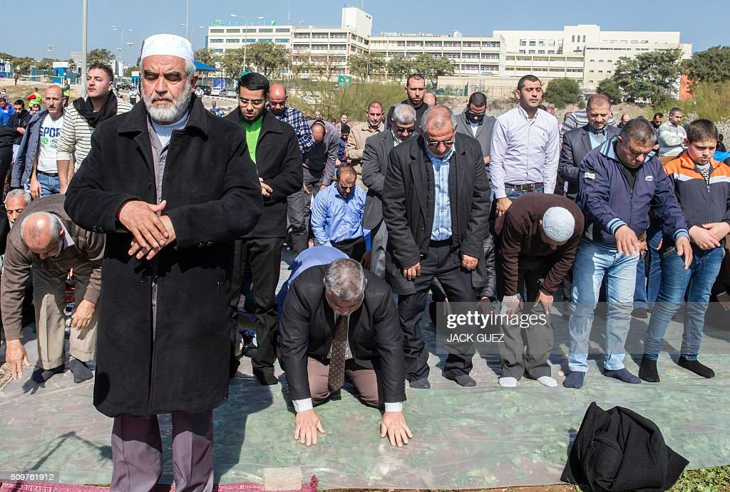 Israeli Arabs and Sheikh Raed Salah (front-L), the leader of the radical northern wing of the Islamic Movement in Israel, takes part in a prayer in support for the release of Mohammed al-Qiq, a Palestinian prisoner on hunger strike, outside the hospital where he is being treated in the northern Israeli town of Afula on February 12, 2016. Ailing Palestinian journalist Qiq will keep up his ten-week hunger strike despite Israel suspending a detention without trial order against him, his lawyer said. / AFP / JACK GUEZ