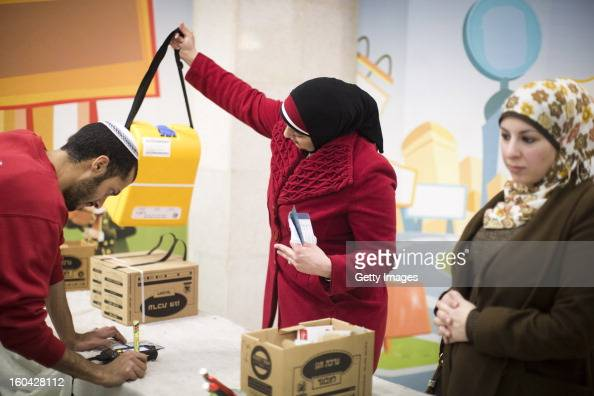 Israeli Arabs collect gas mask kits from a distribution station in a mall January 31 in Pisgat Ze'ev East Jerusalem Israel Israel remains on high...