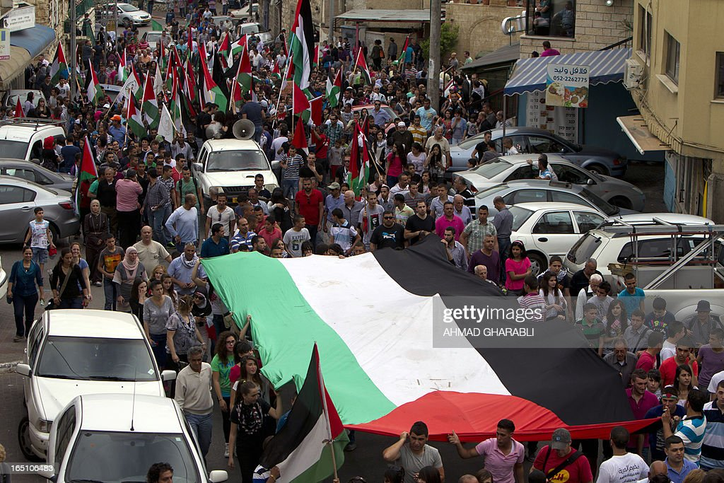 Israeli Arabs deploy a giant Palestinian flag during a rally in the northern Arab-Israeli town of Sakhnin on March 30, 2013 commemorating the 37th anniversary of 'Land Day'. The annual demonstrations mark the deaths of six Arab Israeli protesters at the hands of Israeli police and troops during mass protests in 1976 against plans to confiscate Arab land in the northern Galilee region.