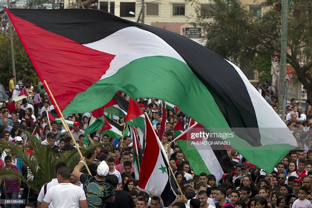 Israeli Arabs wave a giant Palestinian flag during a rally in the northern Arab-Israeli town of Sakhnin on March 30, 2013 commemorating the 37th anniversary of 'Land Day'. The annual demonstrations mark the deaths of six Arab Israeli protesters at the hands of Israeli police and troops during mass protests in 1976 against plans to confiscate Arab land in the northern Galilee region.