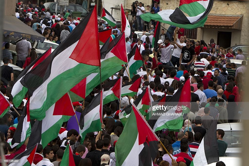 Israeli Arabs wave Palestinian flags during a rally in the northern Arab-Israeli town of Sakhnin on March 30, 2013 commemorating the 37th anniversary of 'Land Day'. The annual demonstrations mark the deaths of six Arab Israeli protesters at the hands of Israeli police and troops during mass protests in 1976 against plans to confiscate Arab land in the northern Galilee region.