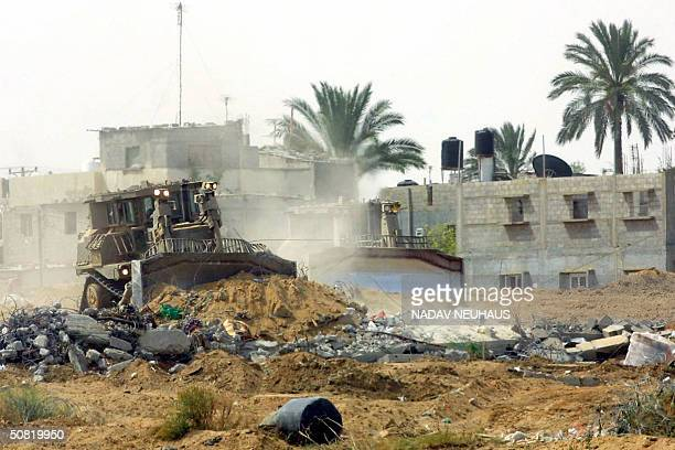 Israeli army bulldozers flatten the area after demolishing houses at the edge of Khan Yunes refugee camp in the southern Gaza Strip 10 May 2004 The...
