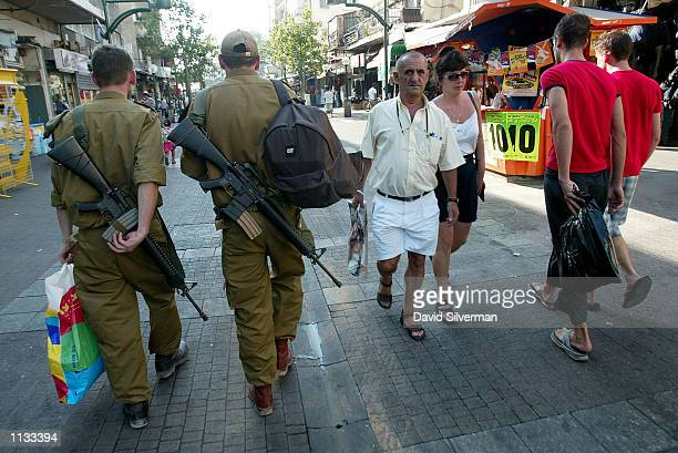 Israeli army conscripts walking to their bus pass a couple and two foreign workers July 18 2002 down the road from the scene of a Palestinian suicide...
