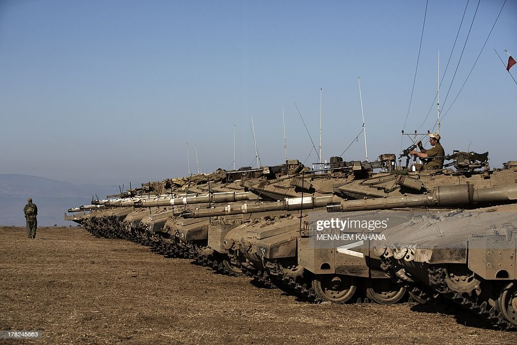 Israeli army Merkava tanks are seen stationed in a deployment training area in the Israeli-annexed Golan Heights near the border with Syria on August 28, 2013. Israel will strike back 'fiercely' if Syria attacks the Jewish state, Prime Minister Benjamin Netanyahu said, as the US mulled military action against President Bashar al-Assad's regime. AFP PHOTO/MENAHEM KAHANA