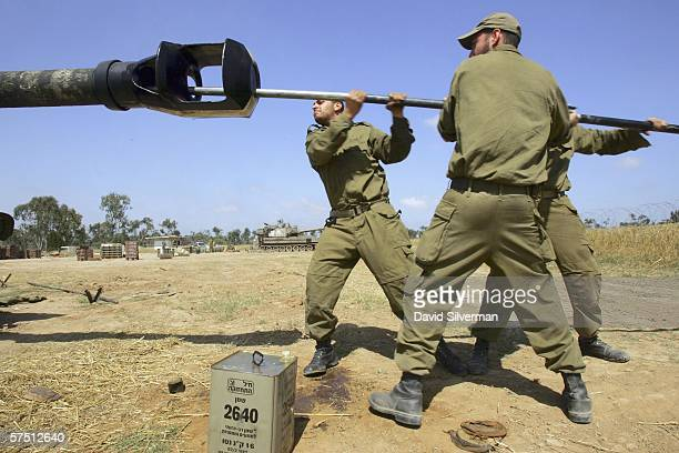 Israeli artillery soldiers who have spent the last two months firing thousands of shells at Palestinian militants in the Gaza Strip clean the barrel...