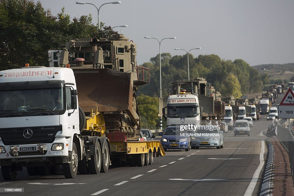 Israeli bed-trucks transport military armoured bulldozers as the convoy leaves a deployment area near the Israel-Gaza Strip border on November 22, 2012, a day after a cease fire was declared between the Jewish state and Hamas. Defence Minister Ehud Barak warned that Israel may resume its attacks on Gaza at any time if a truce that ended a week of bloodshed fails to hold.