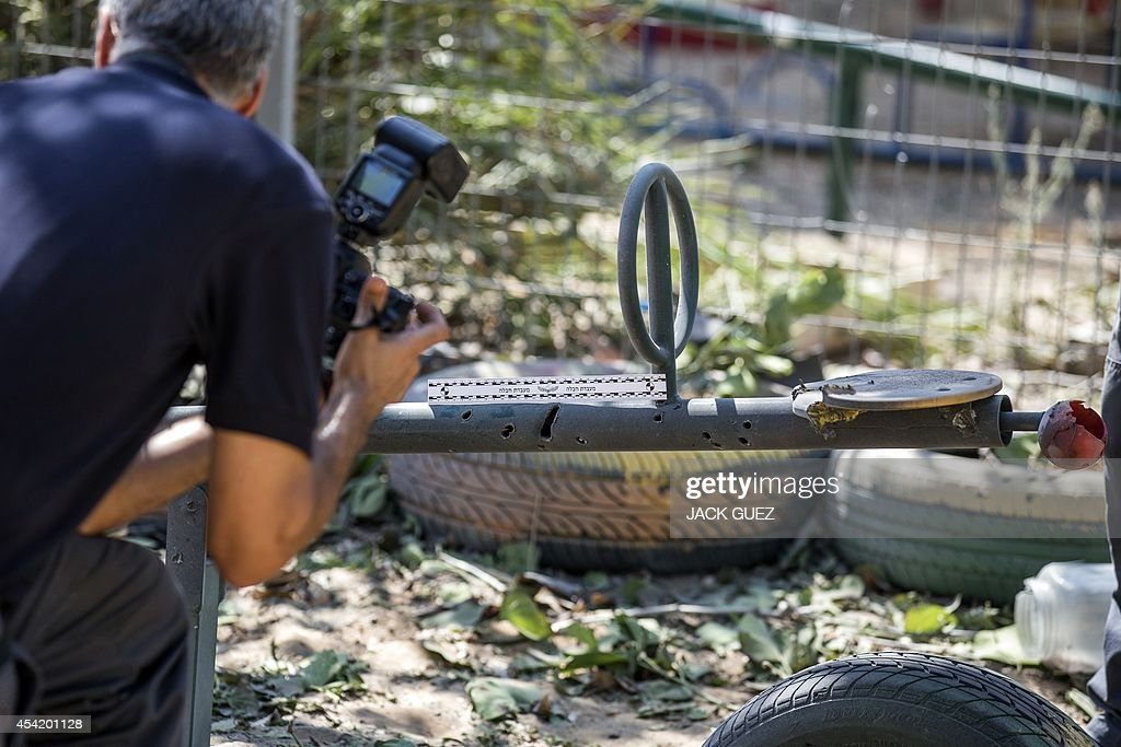 Israeli bomb disposal experts takes photos of the damage caused by a rocket, fired by Palestinian militants from the Gaza Strip, after it landed in the courtyard of a kindergarten in the southern costal Israeli city of Ashdod, on August 26, 2014. Israel upped the pressure on Hamas, with warplanes hitting two Gaza City highrises on day 50 of their conflict as the warring parties mulled a new Egyptian truce proposal.