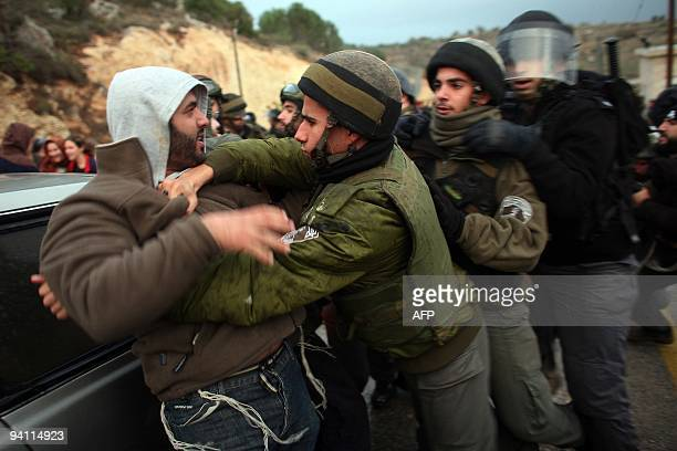 Israeli borde policemen scuffle with Jewish settlers who tried to block a road to prevent entry of government inspectors handing out orders to halt...