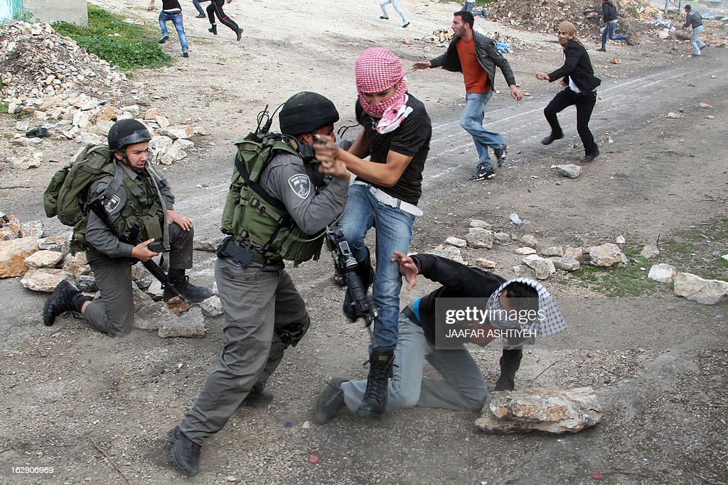 Israeli border guard detain a Palestinian during clashes following a protest against the against the expropriation of Palestinian land by Israel on March 1, 2013, in the village of Kafr Qaddum, near the occupied West Bank city of Nablus. AFP PHOTO/JAAFAR ASHTIYEH