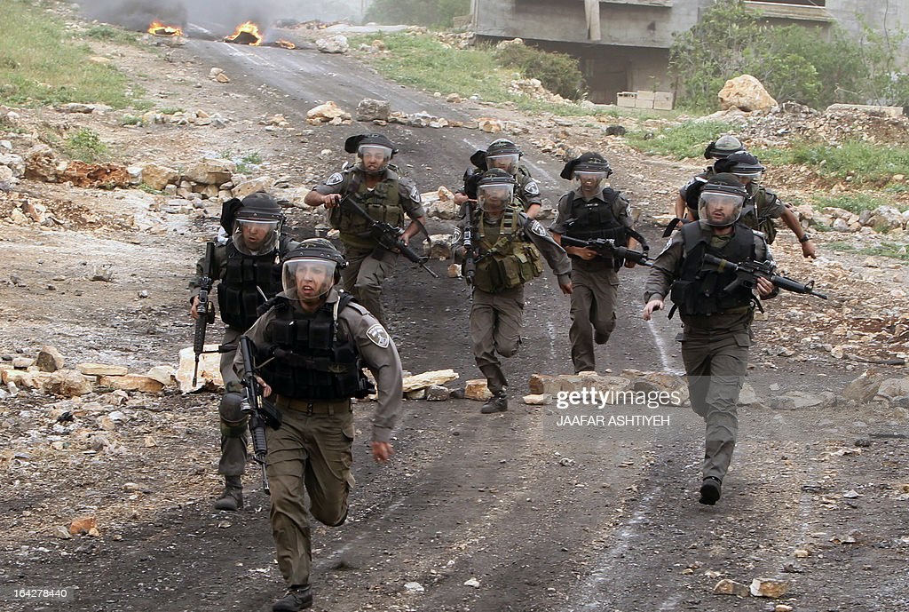 Israeli border guard run after Palestinian protesters during clashes following a protest against the expropriation of Palestinian land by Israel on March 22, 2013, in the village of Kafr Qaddum, near the occupied West Bank city of Nablus.