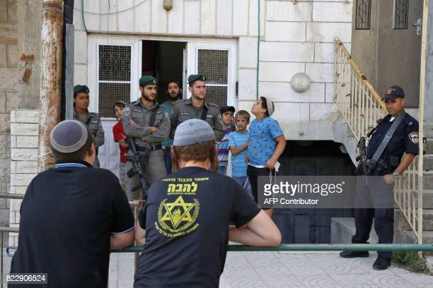 Israeli border guards and police keep watch as a group of Israeli settlers gather at a Palestinian house they have occupied the previous day in the...