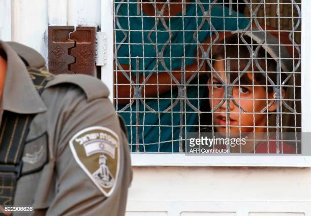 Israeli border guards and police keep watch as a group of Israeli settlers and children gather at a Palestinian house they have occupied the previous...