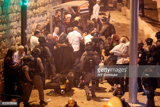 TOPSHOT Israeli border guards attempt to disperse Palestinian Muslim worshippers outside Lions' Gate a main entrance to the AlAqsa mosque compound in...