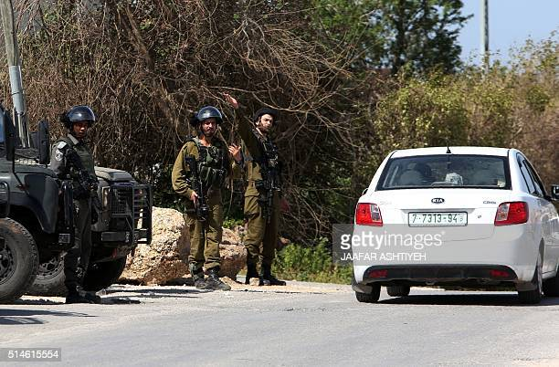 Israeli border guards check a car on March 10 2016 in the West Bank village of Haja near the town of Qalqilya two days after a Palestinian from this...