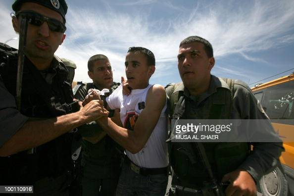 Israeli border guards detain protesters during a demonstration by Palestinian and foreign peace activists against the construction of a section of...