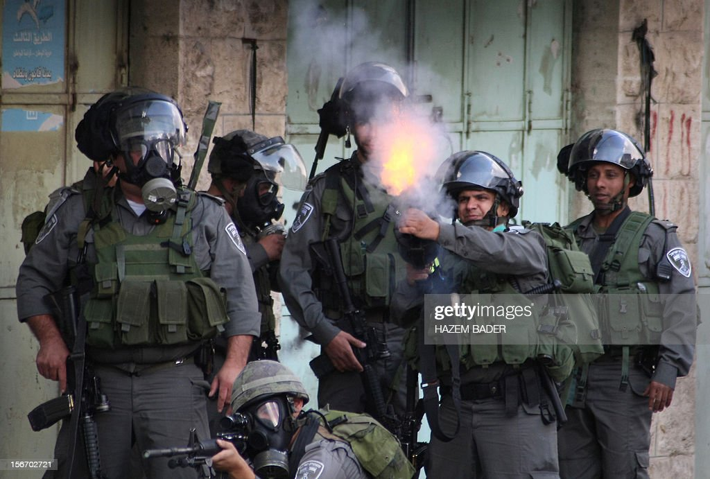 Israeli border guards fire tear gas canister towards Palestinian protestors during clashes in the centre of the divided West Bank city of Hebron, near the Israeli Beit Hadassa settlement, on November 19, 2012. Israeli air strikes killed 21 people in Gaza on Monday, raising the overall death toll to 98 on the sixth day of the relentless bombing campaign.