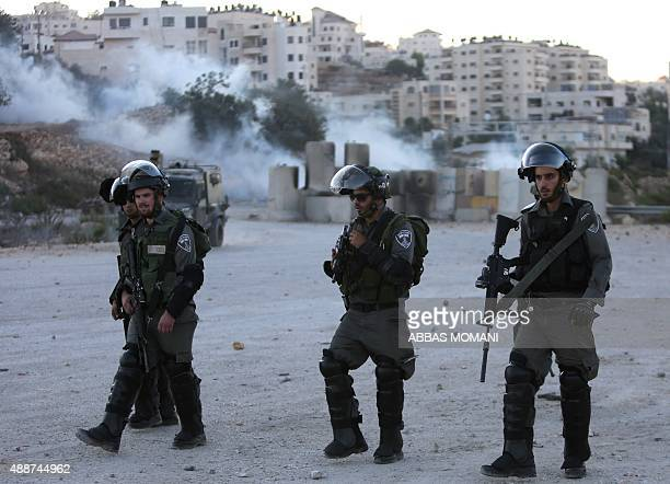 Israeli border guards hold a position Palestinian youth during clashes with Palestinian youths near the Ofer Israeli military prison located near the...