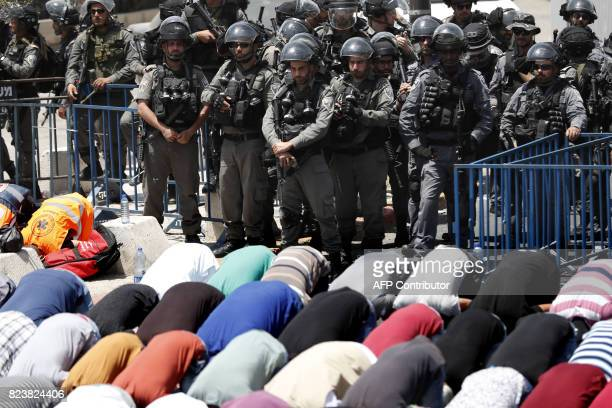 TOPSHOT Israeli border guards keep watch as Palestinian Muslim worshippers pray outside Jerusalem's old city overlooking the AlAqsa mosque compound...
