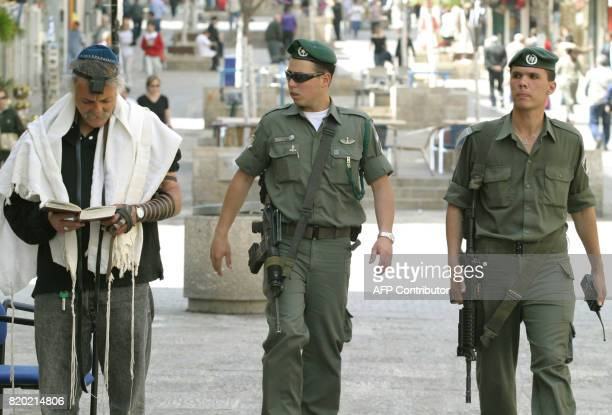 Israeli border guards patrol the streets as a Jewish man wearing a tefillin prays in a pedestrian shopping area of Jerusalem 24 March 2004 as Israel...