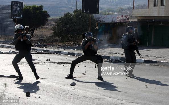 Israeli border guards take aim at Palestinian demonstrators during clashes at the Hawara checkpoint south of the West Bank city of Nablus on October...