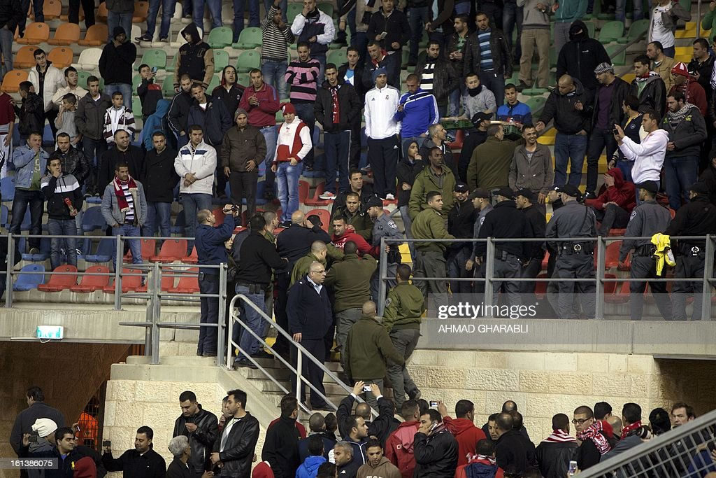 Israeli border police arrest a Bnei Sakhnin supporter during an Israeli championship football match between Beitar Jerusalem and Bnei Sakhnin at the Teddy Kollek Stadium in Jerusalem on February 10, 2013. The Beitar Jerusalem soccer club hosted the Israeli Arab team Bnei Sakhnin in a highly charged atmosphere, only three days after indictments were filed against four Beitar fans over charges relating to racism.