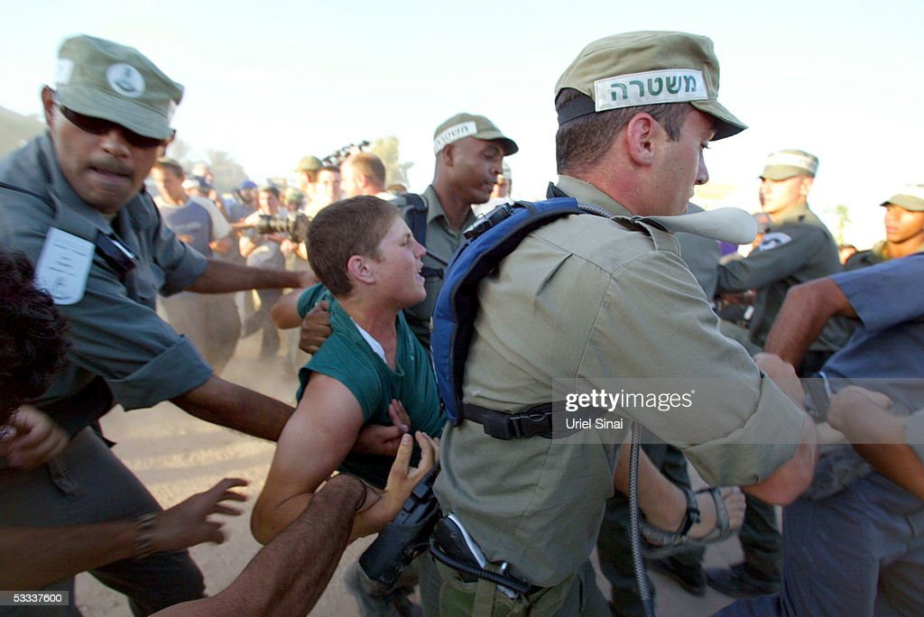 Israeli border police arrest a rightwing Israeli settler during scuffles between the two sides after the army attempted to remove a caravan filled...