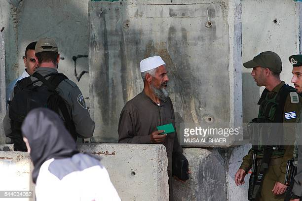 Israeli border police check a Palestinian man's West Bank identity card at an Israeli checkpoint between the town of Bethlehem and Jerusalem as he...