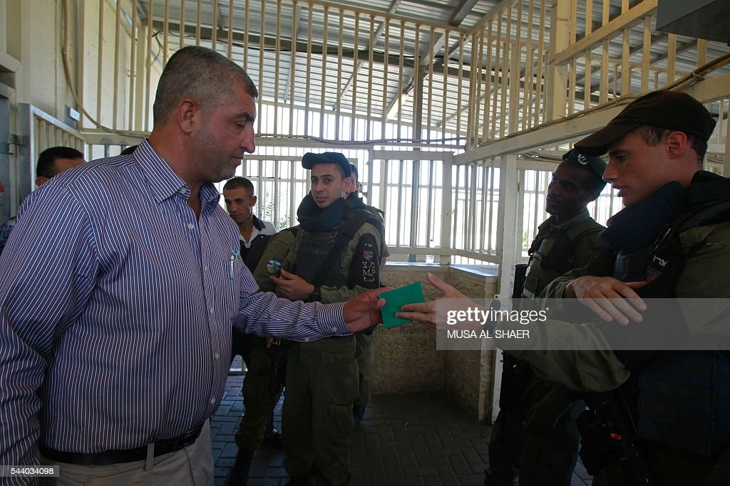 Israeli border police check a Palestinian man's West Bank identity card at an Israeli checkpoint between the town of Bethlehem and Jerusalem, as he heads to Jerusalem's Al-Aqsa Mosque compound on the forth and last Friday of the Muslim holy month of Ramadan on July 1 , 2016. Israeli authorities announced on June 28 they were closing Jerusalem's flashpoint Al-Aqsa mosque compound to non-Muslim visitors until the end of the Muslim holy month of Ramadan after a series of clashes between worshippers and Israeli police. Clashes have been taking place every morning since the beginning of the week over Jewish visits to the site, with youths throwing stones and security forces firing tear gas and sponge-tipped bullets. / AFP / MUSA