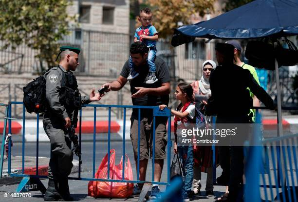 Israeli border police check identification documents as they stand guard outside Damascus Gate a main entrance to Jerusalem's Old City on July 15...