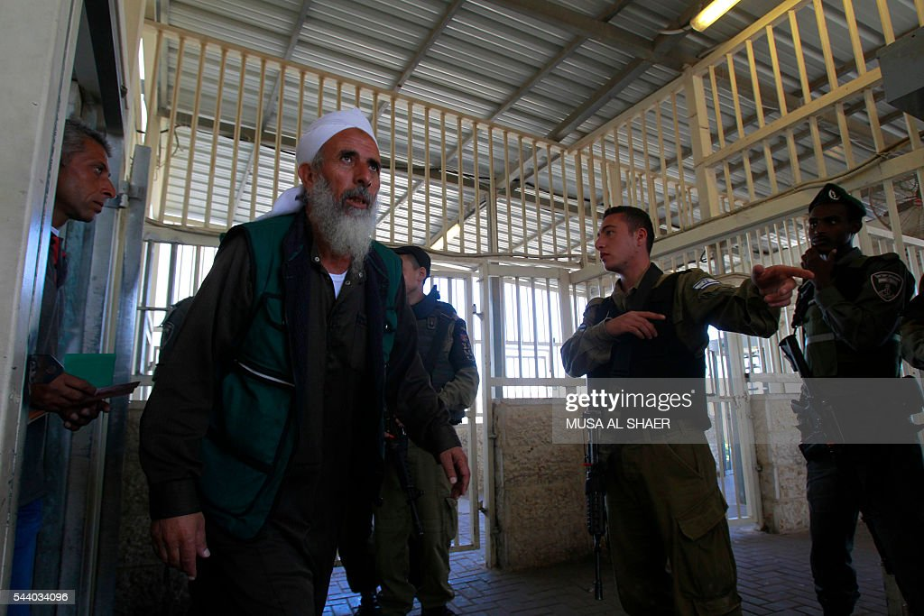 Israeli border police check Palestinian men's West Bank identity cards at an Israeli checkpoint between the town of Bethlehem and Jerusalem, as he heads to Jerusalem's Al-Aqsa Mosque compound on the forth and last Friday of the Muslim holy month of Ramadan on July 1 , 2016. Israeli authorities announced on June 28 they were closing Jerusalem's flashpoint Al-Aqsa mosque compound to non-Muslim visitors until the end of the Muslim holy month of Ramadan after a series of clashes between worshippers and Israeli police. Clashes have been taking place every morning since the beginning of the week over Jewish visits to the site, with youths throwing stones and security forces firing tear gas and sponge-tipped bullets. / AFP / MUSA