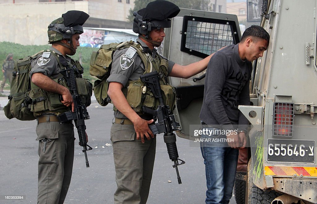 Israeli border police detain a Palestinian demonstrators during a protest in solidarity with hunger-striking Palestinian prisoners in the city of Nablus on February 22, 2013. Palestinians demanding the release of hunger-striking prisoners clashed with Israelis in the West Bank and east Jerusalem, as three fasting inmates were taken to hospitals. AFP PHOTO /JAAFAR ASHTIYEH