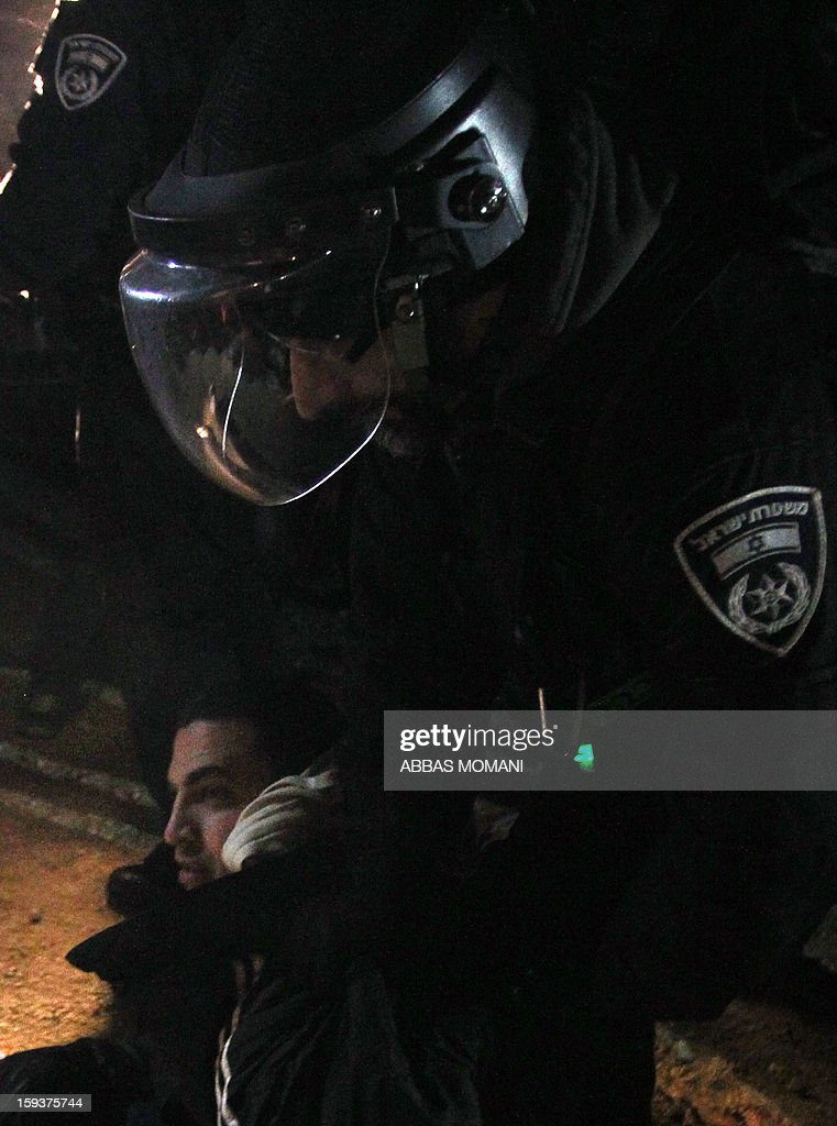 Israeli border police evict an Palestinian protester (bottom) from the scene in the controversial West Bank area known as E1 between Israeli annexed east Jerusalem and the settlement of Maaleh Adumim early on January 13, 2013. Israeli police early on January 13 evicted Palestinian protesters from a hilltop camp they set up in a West Bank area slated for Jewish settlement, police and witnesses said. AFP PHOTO / ABBAS MOMANI