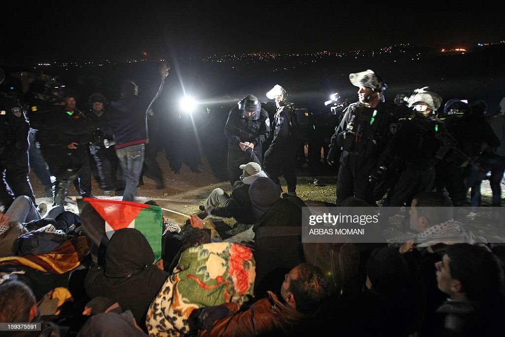 Israeli border police (top) evict Palestinian protesters (bottom) from the scene in the controversial West Bank area known as E1 between Israeli annexed east Jerusalem and the settlement of Maaleh Adumim early on January 13, 2013. Israeli police early on January 13 evicted Palestinian protesters from a hilltop camp they set up in a West Bank area slated for Jewish settlement, police and witnesses said. AFP PHOTO / ABBAS MOMANI