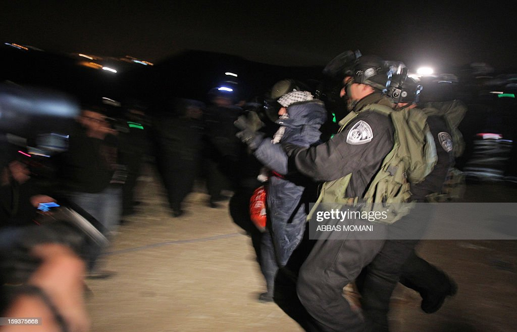 Israeli border police evict Palestinian protesters from the scene in the controversial West Bank area known as E1 between Israeli annexed east Jerusalem and the settlement of Maaleh Adumim early on January 13, 2013. Israeli police early on January 13 evicted Palestinian protesters from a hilltop camp they set up in a West Bank area slated for Jewish settlement, police and witnesses said. AFP PHOTO / ABBAS MOMANI