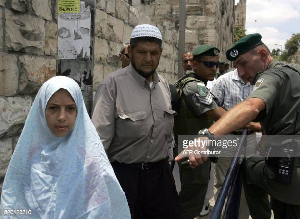 Israeli border police officers ask for the ID of a Palestinian man and his daughter wanting to enter into the old city for Friday noon prayers at the...