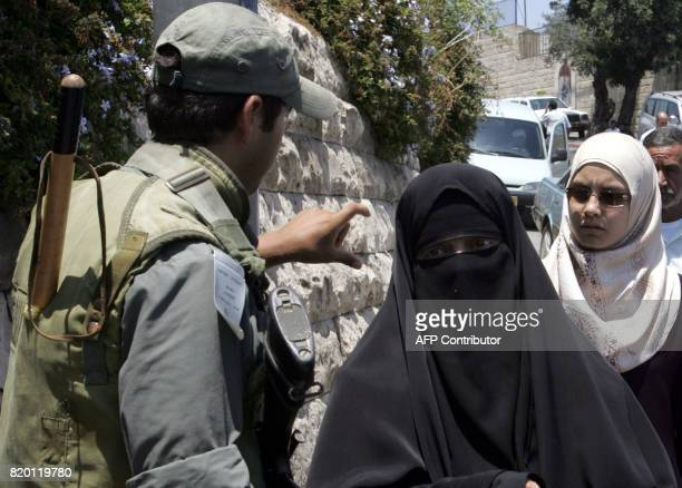 Israeli border police officers asks for an ID card from a Muslim orthodox woman as she enters the old city in annexed east Jerusalem 21 July 2006...