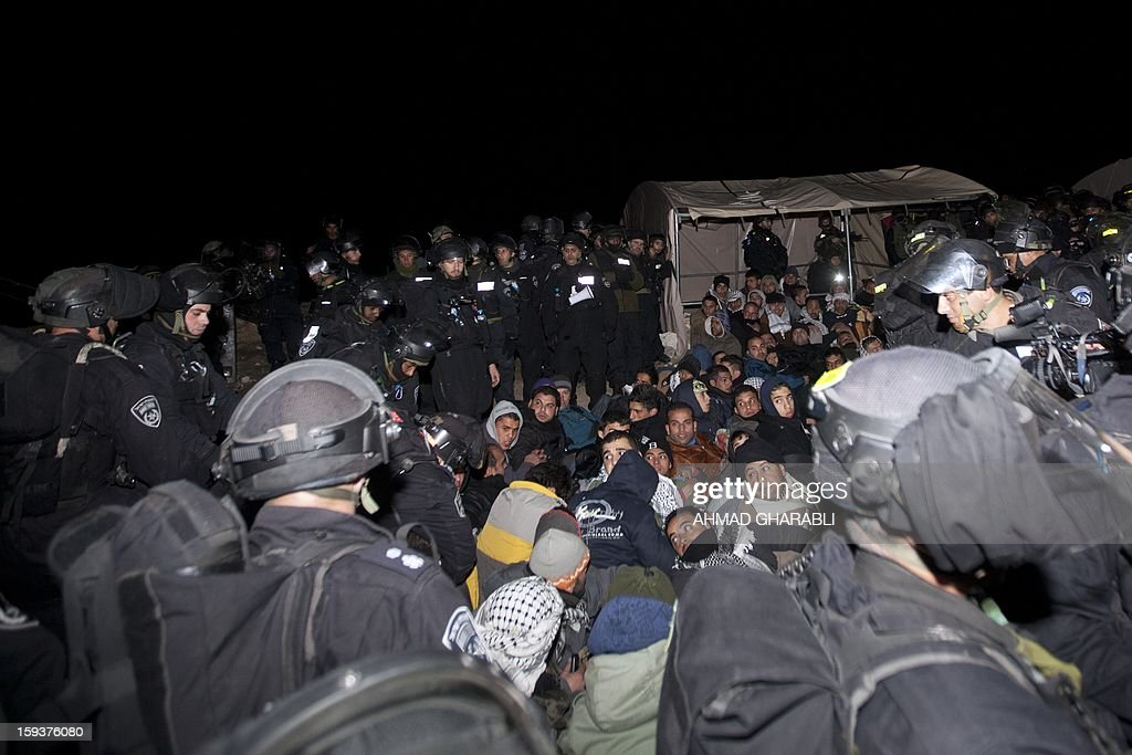 Israeli border police prepare to evacuate Palestinian protesters from the scene in the controversial West Bank area known as E1 between Israeli annexed east Jerusalem and the settlement of Maaleh Adumim early on January 13, 2013. Israeli police early on January 13 evicted Palestinian protesters from a hilltop camp they set up in a West Bank area slated for Jewish settlement, police and witnesses said.