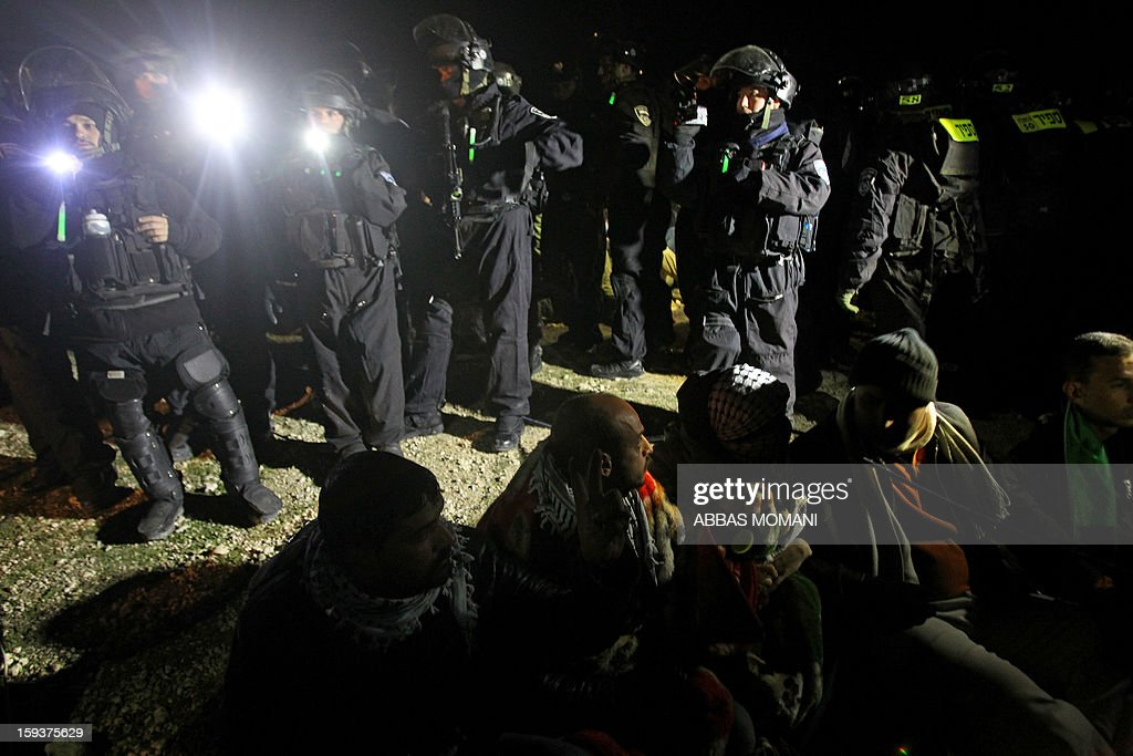 Israeli border police (top) prepare to evict Palestinian protesters (bottom) from the scene in the controversial West Bank area known as E1 between Israeli annexed east Jerusalem and the settlement of Maaleh Adumim early on January 13, 2013. Israeli police early on January 13 evicted Palestinian protesters from a hilltop camp they set up in a West Bank area slated for Jewish settlement, police and witnesses said. AFP PHOTO / ABBAS MOMANI