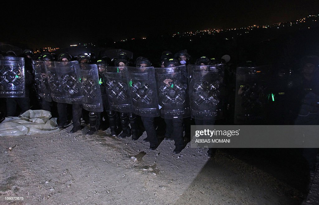 Israeli border police prepare to search an outpost of tents as they prepare to evacuate Palestinian protesters from the scene in the controversial West Bank area known as E1 between Israeli annexed east Jerusalem and the settlement of Maaleh Adumim early on January 13, 2013. Israeli police early on January 13 evicted Palestinian protesters from a hilltop camp they set up in a West Bank area slated for Jewish settlement, police and witnesses said. AFP PHOTO / ABBAS MOMANI
