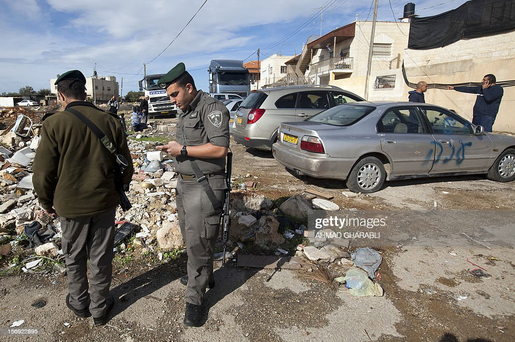 Israeli border police stand next to a car with a graffiti reading in Hebrew 'Gaza: the price to pay' in the Palestinian neighborhood of Shuafat in Israeli annexed East Jerusalem, , on November 25, 2012. Unknown assailants vandalized 8 cars belonging to Palestinians, apparently in retaliation for the recent events in Gaza, the police said today. AFP PHOTO / AHMAD GHARABLI
