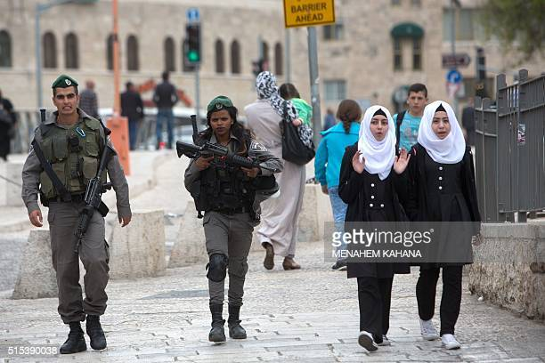 Israeli border police walk next to Palestinian girls during a patrol near Damascus Gate of Jerusalem's Old City on March 13 2016 / AFP / MENAHEM...