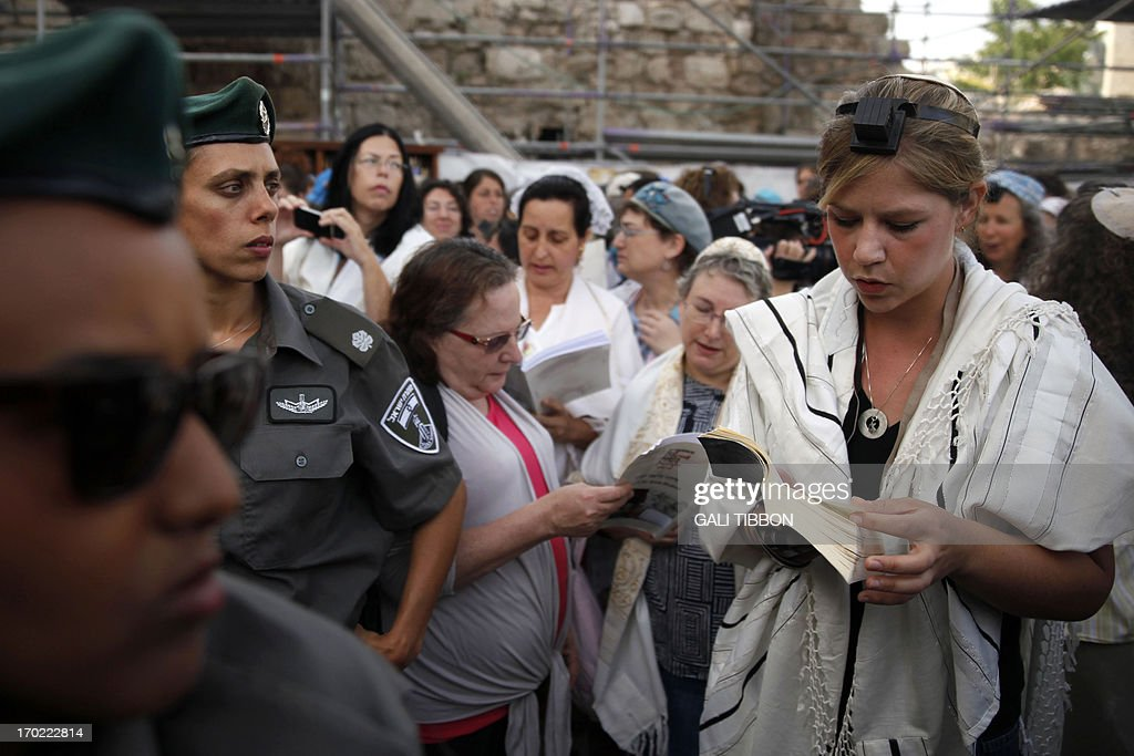Israeli Border Police women stand guard near members of the liberal Jewish religious group Women of the Wall wearing phylacteries and the 'Tallit' shawl, traditional Jewish prayer apparel for men, as they pray at the Western Wall in Jerusalem's Old City on June 9, 2013 marking the first day of the Jewish month of Tamuz. AFP PHOTO/GALI TIBBON