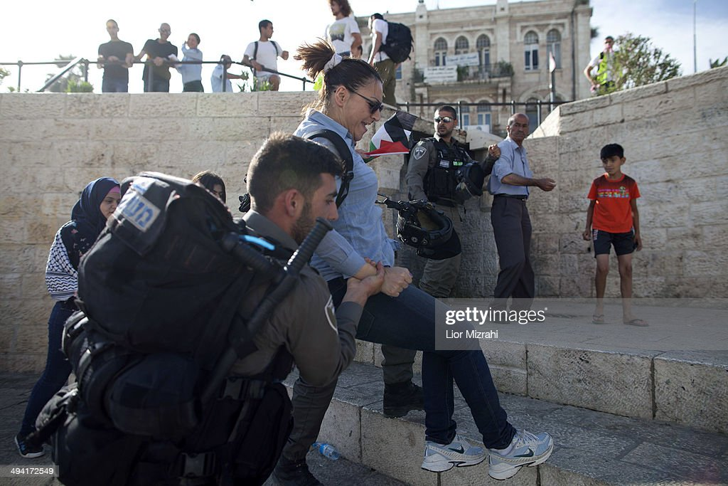 Israeli border policeman detain a Palestinian woman as Israelis march marking Jerusalem Day on May 28, 2014 outside Jerusalem's old city, Israel. Israel is celebrating the anniversary of the 'unification' of Jerusalem, marking 47 years since it captured mainly Arab east Jerusalem during the 1967 Middle East war.