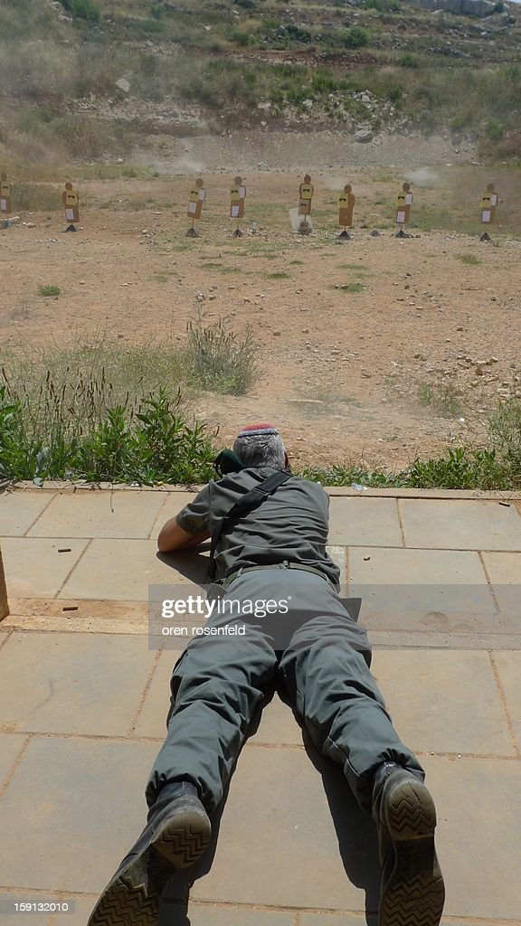 CONTENT] Israeli Border Policeman shooting in a firing range south of Jerusalem at cardboard targets.