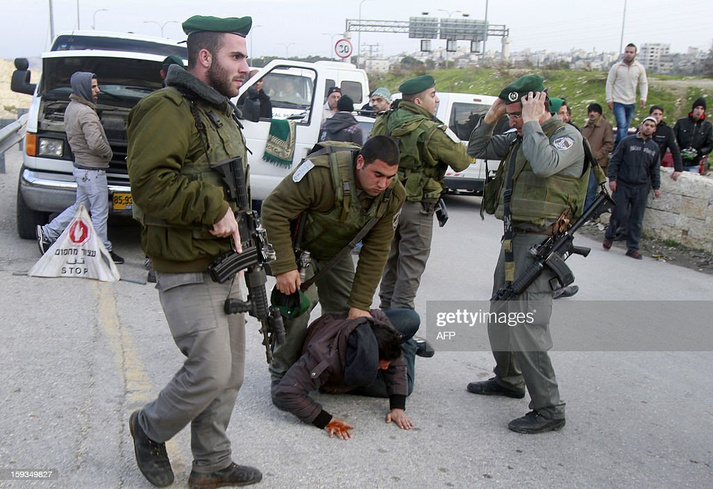 Israeli border policemen arrest a Palestinian man at the entrance of the village of Zayem, as he was on his way to join an 'outpost' named Bab al-Shams ('Gate of the Sun') between Jerusalem and the Jewish settlement of Maale Adumim in the Israeli-occupied West Bank, in an area where Israel has vowed to build new settler homes, on January 12, 2013. Israeli authorities quickly issued expulsion orders, but activists' lawyers successfully petitioned the supreme court at night for a stay. AFP PHOTO/MUSA AL SHAER
