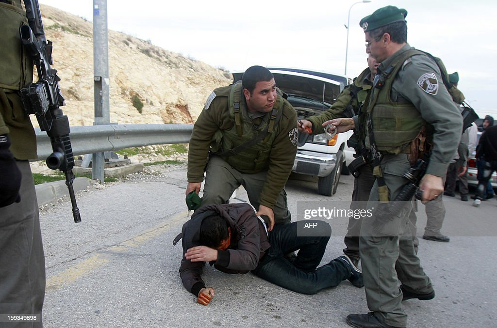 Israeli border policemen arrest a Palestinian man at the entrance of the village of Zayem, as he was on his way to join an 'outpost' named Bab al-Shams ('Gate of the Sun') between Jerusalem and the Jewish settlement of Maale Adumim in the Israeli-occupied West Bank, in an area where Israel has vowed to build new settler homes, on January 12, 2013. Israeli authorities quickly issued expulsion orders, but activists' lawyers successfully petitioned the supreme court at night for a stay.