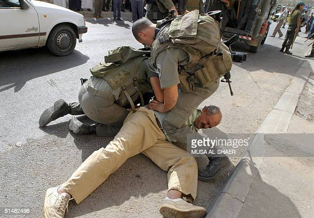 Israeli border policemen arrest a Palestinian man who was trying to cross from the West Bank town of Bethlehem to Jerusalem to pray at the AlAqsa...