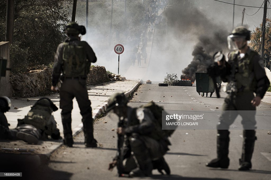 Israeli border policemen confront a group of Palestinian stone throwers during clashes following the funeral of Mohammad Asfour in the West Bank village of Abud on March 8, 2013. Asfour died of his wounds on March 7, after he was hit by a rubber-coated steel bullet during a demonstration over the death of a Palestinian prisoner in Israeli custody in February.