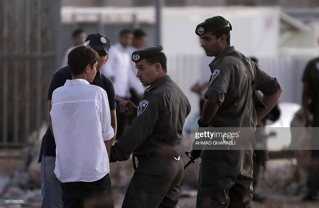 Israeli border policemen escort an ultra-Orthodox Jewish boy from the Ramat Shlomo neighbourhood on September 1, 2012 after a group of ultra-Orthodox Jews hurled stones at Palestinian homes in the Shuafat refugee camp of annexed east Jerusalem, injuring one person, police said.